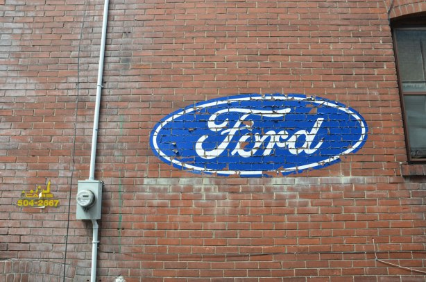 red brick wall, side of a house, with a loarge blue and white Ford logo on it.