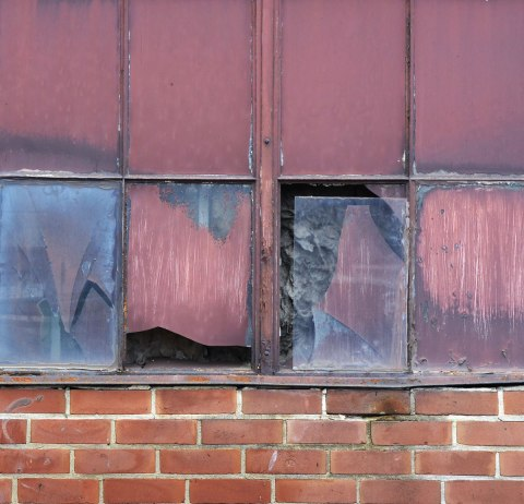 part of a wall, red brick on the bottom, maroon coloured metal sheeting on the top and 4 dirty and broken panes of glass in the center