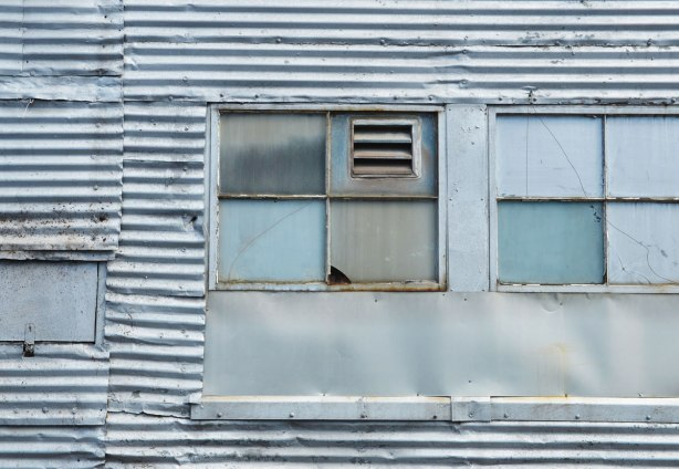 An old corrugated metal building with a window insert that has been filled in except for a small vent.