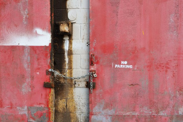 part of two old rusty and messy red doors on an old white building. There is a chain between the doors. The door on the right has the words No Parking stencilled onto it.