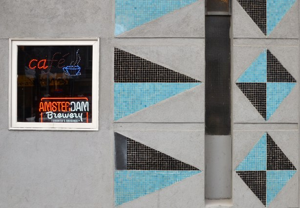 close up of part of the exterior wall of the Rex Hotel on Queen Street West, black and blue mosaic triangles on a grey wall. A small window is in the picture with neon lights with ad for Amsterdam brewery