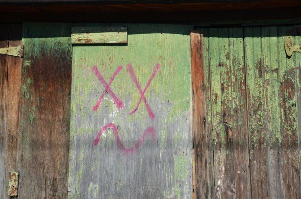 An old wood that was painted green but the paint is faded. Someone has made a face with two large X's for eyes and a squiggly line for a mouth, all lines in pink