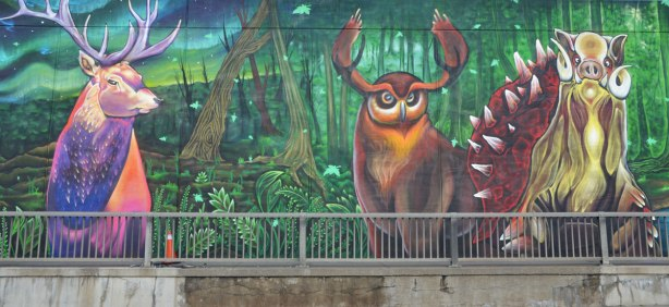 part of a street art mural - three animals, a warthog with spikey back, a deer, and another animal with antlers and a roundish face