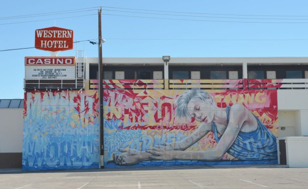 mural on the side of the WEstern Hotel and casino, a woman is sitting, eyes closed, arms outstretched in front of her.