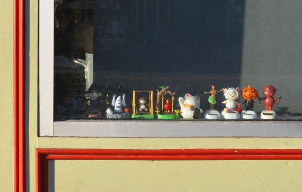 A line of toy figurines on a window sill in the window of a restaurant