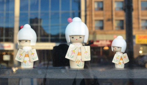 three little Japanese wooden dolls with white hair and white kimonos standing inside a window. Reflections of the stores across the street are behind them.