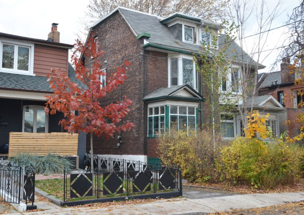 a large brick semi-detached house with trees around it in fall foilage. The side of the house closest to the camera has a glassed in porch. To the left is a small house with a black metal fence around the front yeard. The fence has diamond shaped black metal pieces joined together in squares.
