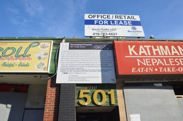 development proposal sign above a large number 501, with an office/retail for lease sign above it.