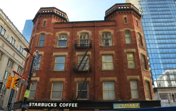 Oddfellows Hall, a large brick building with two hexagonal turrets, brick, now a Starbucks on the ground floor.