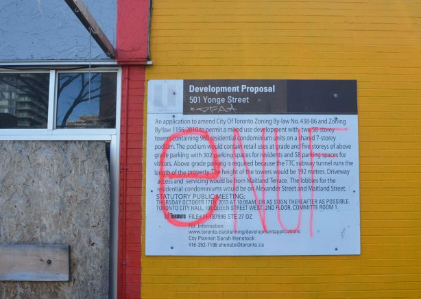 development proposal sign on a yellow wall that someone has written enuf on in big pink letters
