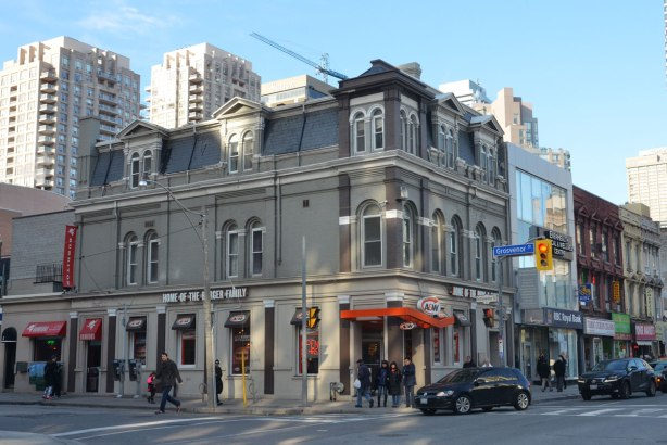Three storey older grey building on a downtown corner.