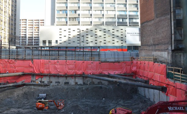 A hole in the ground on Yonge Street for construction of a building.