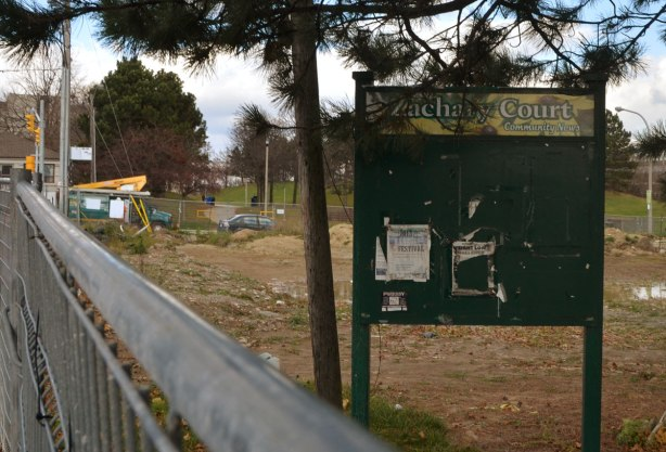 An old sign for community notices that is now empty because the area is fenced off for demolition