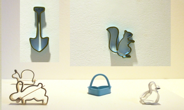 six little rings and broaches made to look like cookie cutters, a shovel, a squirrel, a rabbit, a heart, a duck and a snail.