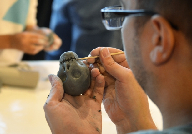 close up picture of a man putting details on a small clay skull with a toothpick