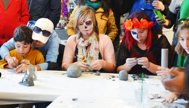 Two girls with day of the dead face paint on are making clay skulls. A young boy is also at the table making a skull, his mother is helping him.