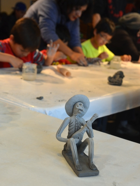 A small figurine made of a clay of a skeleton wearing a sombraro and playing a guitar is in the foreground, kids making clay skulls at a table are in the background.