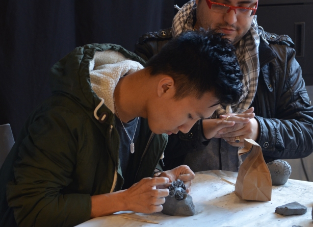 A young man carefully adds tiny clay roses to a clay skull that he has made.