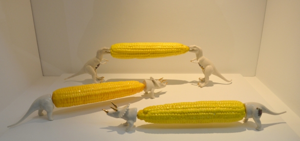 sculptures of cobs of corn, three, each with dinosaur corn cob holders.