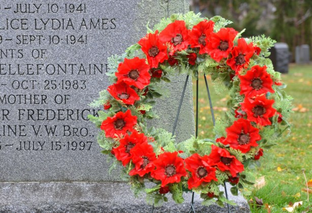 poppy wreath beside a tombstone in a cemetery