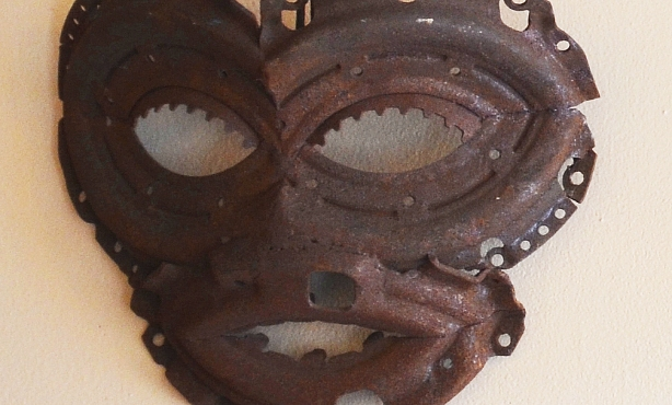 close up of a mask hanging on a wall. It's made of rusty metal car parts welded together