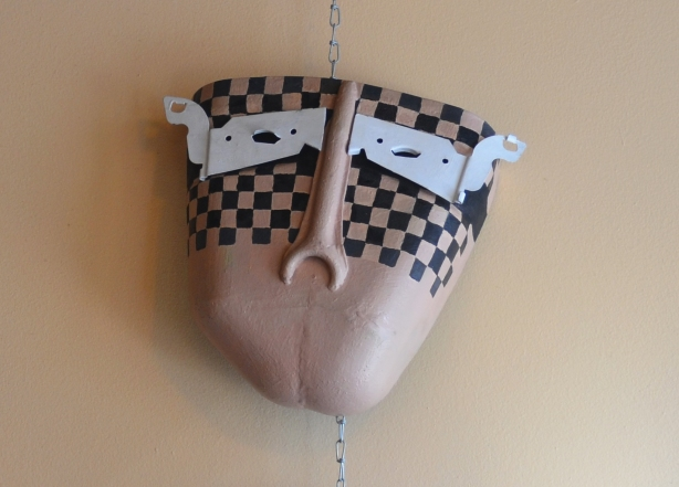 A mask in beige, black and white mounted on the wall. The nose is a wrench. The white part looks like a mask across the eyes of the mask