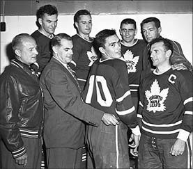 Old black and white picture from the Hockey Hall of Fame, showing Syl Apps (after retirement from hockey) and George Armstrong after Armstrong was given number 10 Maple Leaf jersey to wear.