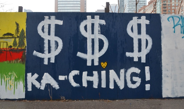 A wood plywood fence painted blue. Someone has painted three large white dollar signs on as well as the word ka-ching.