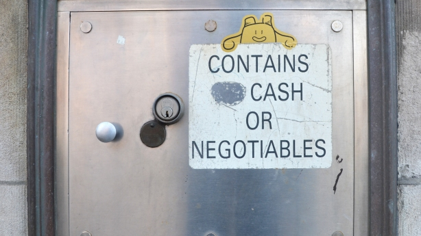 A little yellow sticker on a bank night deposit box, looks like a little smiling creature looking over the sign that says contains no cash or negotiables, except that the word no has been scratched out