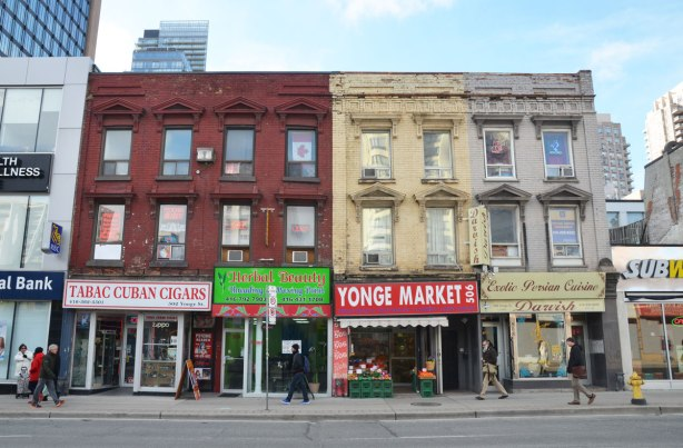 Three three storey buildings in a row, old brick buildings, on Yonge St in downtown toronto, 502, 504 and 506. Yonge Market, Persian restaurant, a Cuban cigar store.