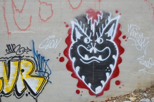 graffiti under a bridge, black deveilish face with horns, beard and teeth, black face, white details, red around it