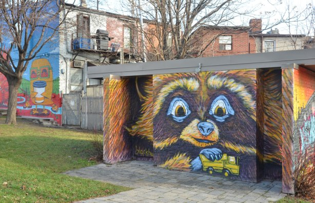mural by blackburn of a raccoon, or similar creature, playing with a yellow toy truck, painted on the side of a building in a park