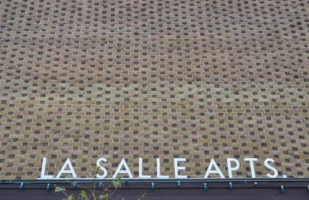 Part of a low rise apartment building, over the door, no windows. Checkerboard pattern in the bricks. The words La Salle Apts in large white letters across the bottom of the picture.
