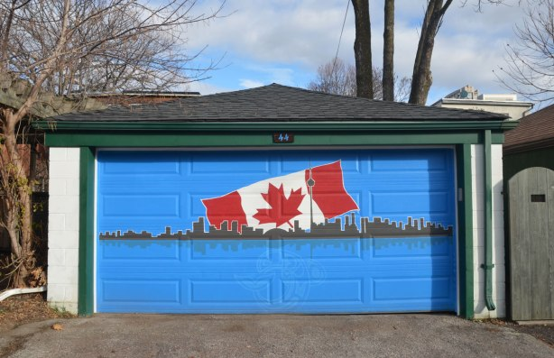 painting on a bright blue garage door of the Toronto skyline with a large Canadian flag behind ithe skyline