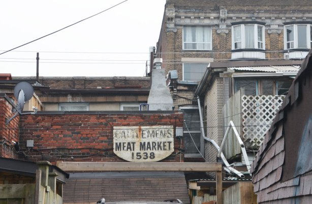 old sign on the back of a building that says Cattlemens meat market 1538