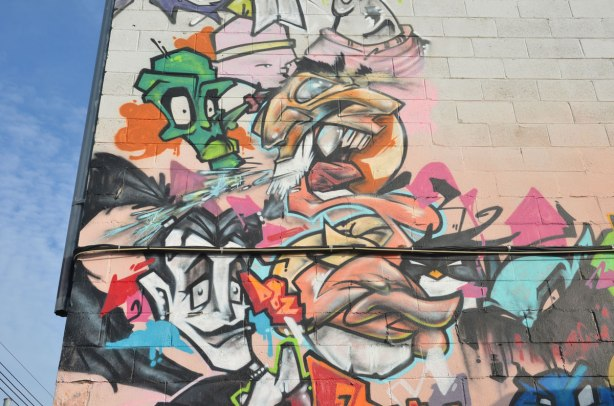 part of a mural with a lot of heads, a man, a green character, amongst others, high on a wall