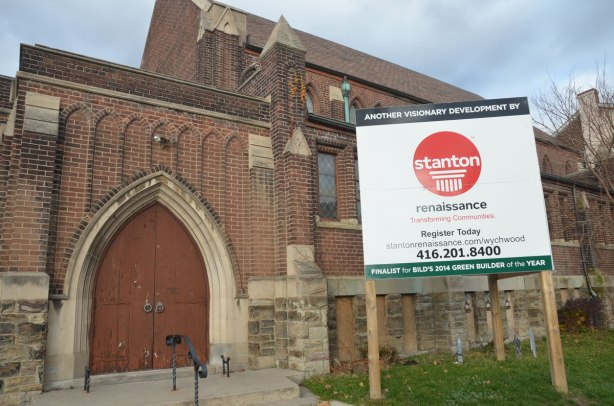 An old brick church at a corner. It is now empty. There is a large sign in front of it advertising Stanton developments.