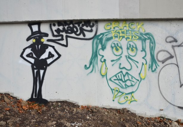 line drawing of a skinny man wearing a top hat beside head of a caricature of Queen Elizewbth in green and yellow. The words, Crack Kills