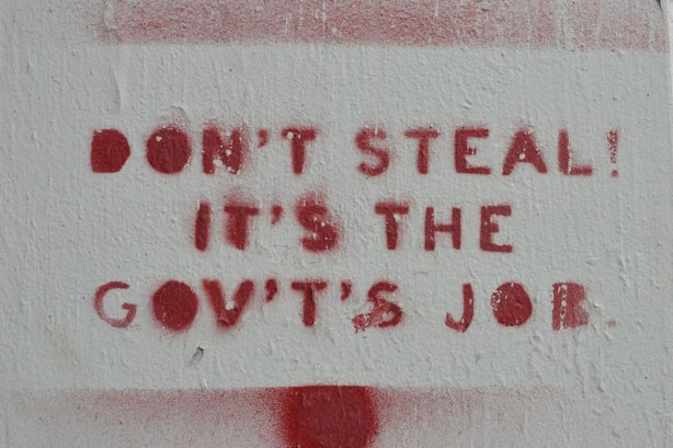 stencil, on concrete, in red, words that sat: Don't steal it's the gov't's job