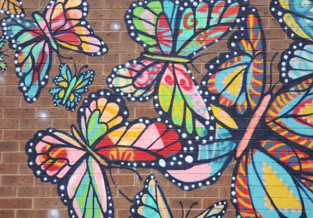 part of a mural on a brick wall, multicolour butterflies
