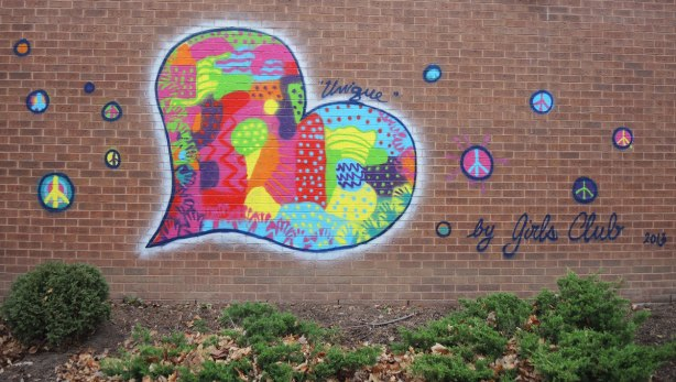 A mural of a large multicoloured heart with peace symbols in circles floating around it. Words: by Girls Club 2013, 'unique'