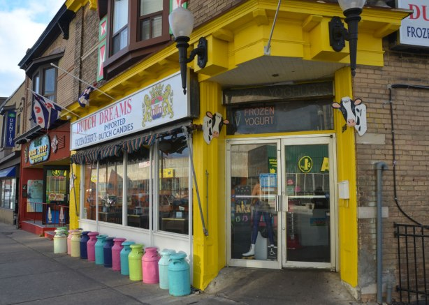 bright yellow entranceway, a line of different coloured milk cans along the exterior wall, sign says Dutch Dreams, candy and ice cream.