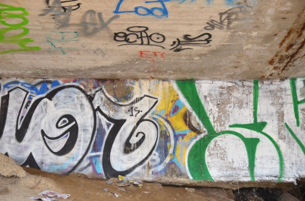 graffiti under a raised parking lot