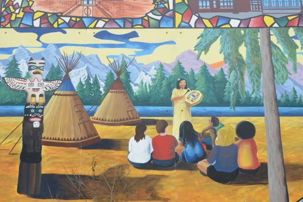 a group of an indigenous peoples are sitting and listening to a woman who is holding a drum. two teepees are in the picture as well