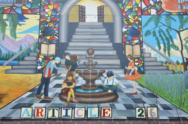 education mural, stairwell with fountain in front of it, stained glass windows on either side