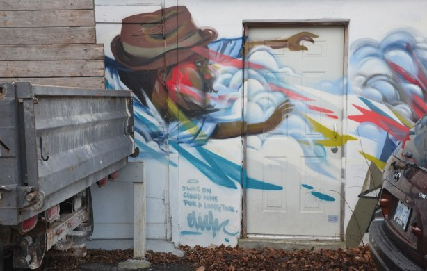 part of an elicser piece on a garage door but a car and a truck are parked in front of the rest. A man in a brown hat is blowing against a door, streams of wind coming from his mouth and clouds are around him, words say I was on cloud nine for a long time.