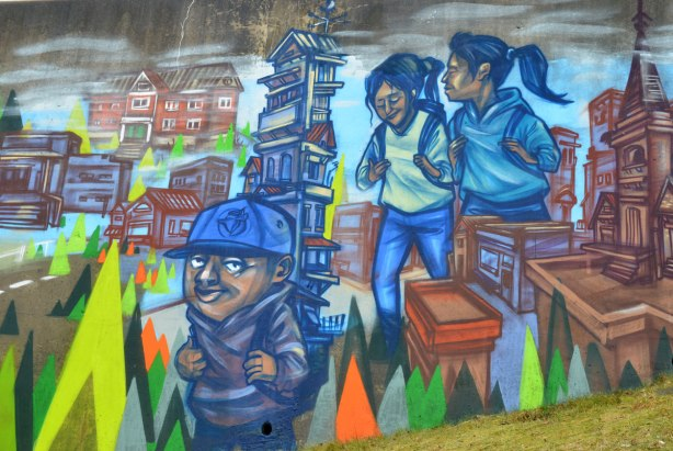 part of a mural by elicser, students with backpacks walking, a boy with a Blue Jays baseball cap.