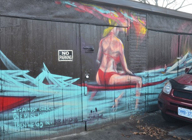 woman in a red bikini sitting on a long board in the water, painted on a garage door, car parked in front partially obscuring it.
