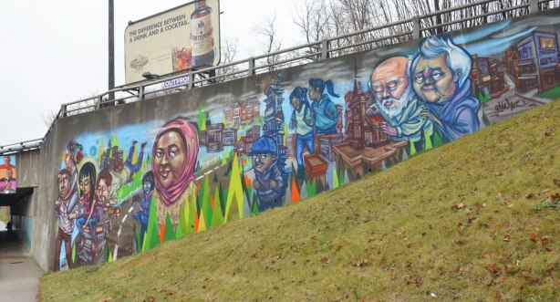 a mural by elicser showing different people, on an underpass on Sheppard Ave East. An older couple, a woman in a pink head scarf, some students, some men and women.