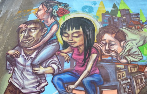 part of a mural by elicser, a group of 4 people, 2 men and 2 women. One of the women is on the shoulders of one of the men.